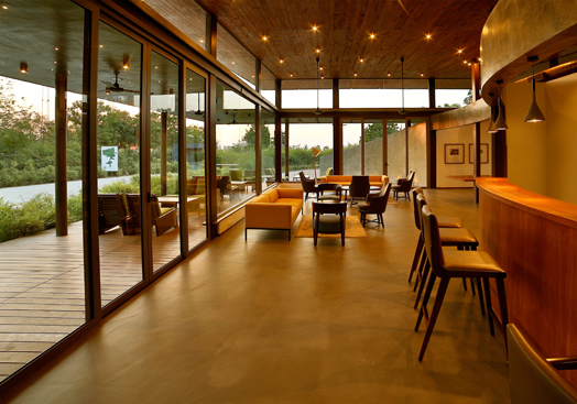 spacious indoors connecting with outdoors via the floor-to-ceiling glass windows