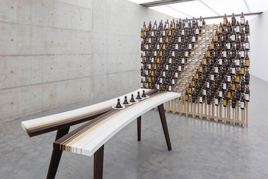 vertical craft beer bottles on curved tasting table