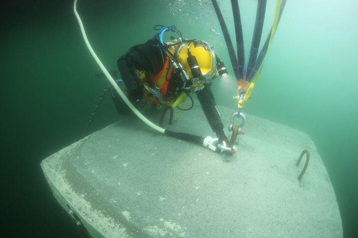 diver connects a rope to install the pier into place